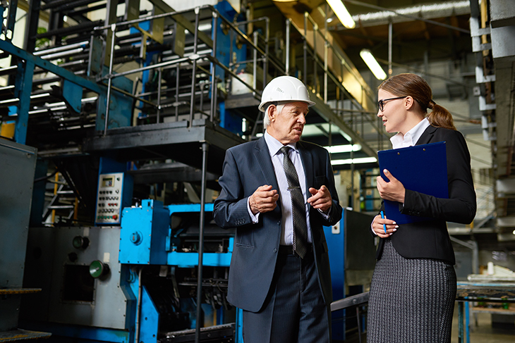 Businesswoman and older businessman in a hard hat having a conversation inside a factory.
