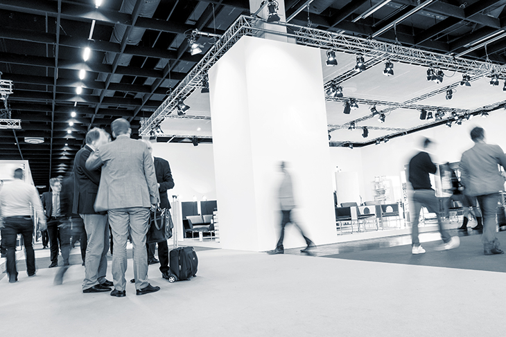 Black-and-white, low-angle photo of attendees walking the floor of a trade show in a large convention center.