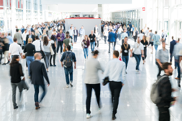 Wide angle photo of attendees walking through a crowded hallway at a convention.