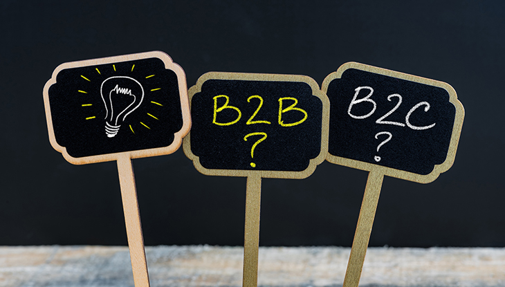 Three signs reading B2B? And B2C? In front of black background with one sign that has a lightbulb illustration.
