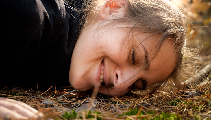 lady laying on the ground on grass and pine needles