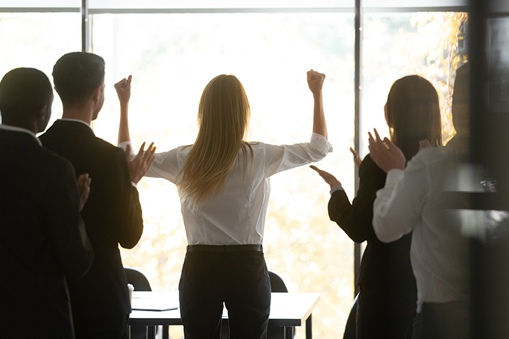 Motivated successful female executive business woman leader get team applause raise hands standing at window celebrating professional victory
