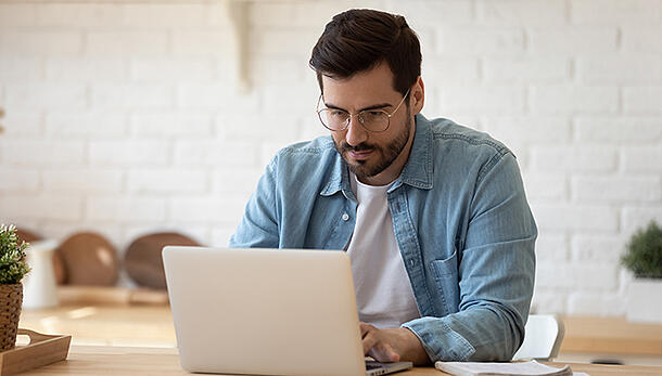man with glasses wearing blue denim shirt working on laptop