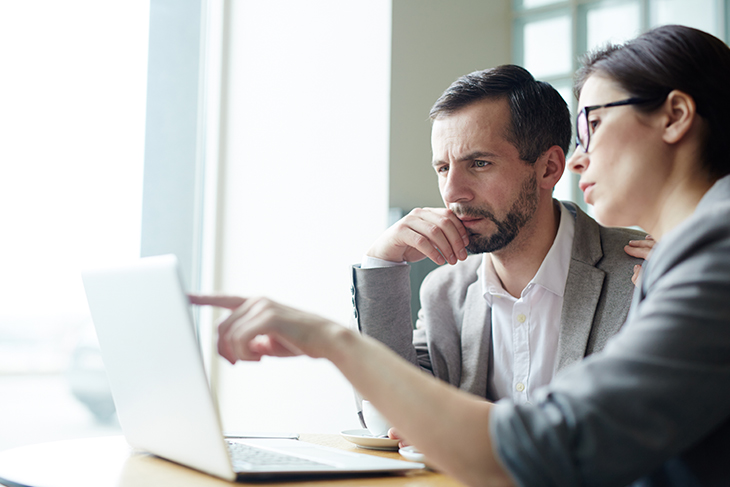 Man and woman looking intently at a laptop computer screen