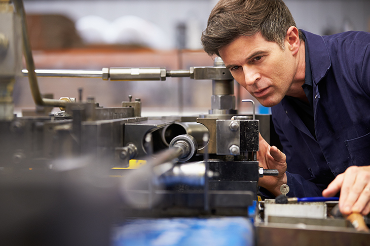Male engineer carefully inspecting a hydraulic tube while operating a tube bender