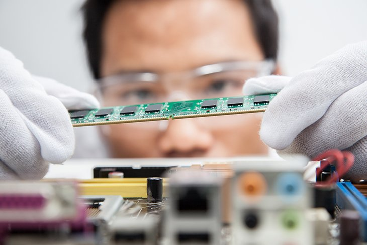 Close up of circuit board being inspected by an engineer in white gloves and safety glasses