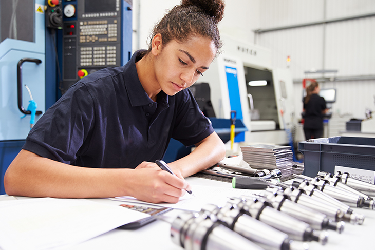 Young woman working on manufacturing product design in front of a CNC machine