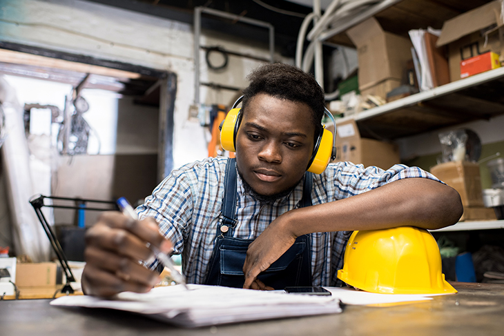 Young African-American man seated at a table doing paperwork in a factory setting