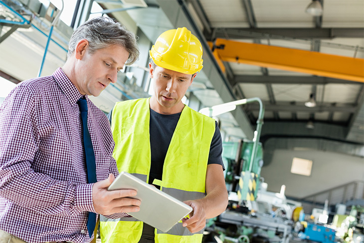 Two co-workers in manufacturing plant reviewing documents on tablet