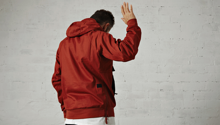 young man in red jacket shows us his back and waves goodbye