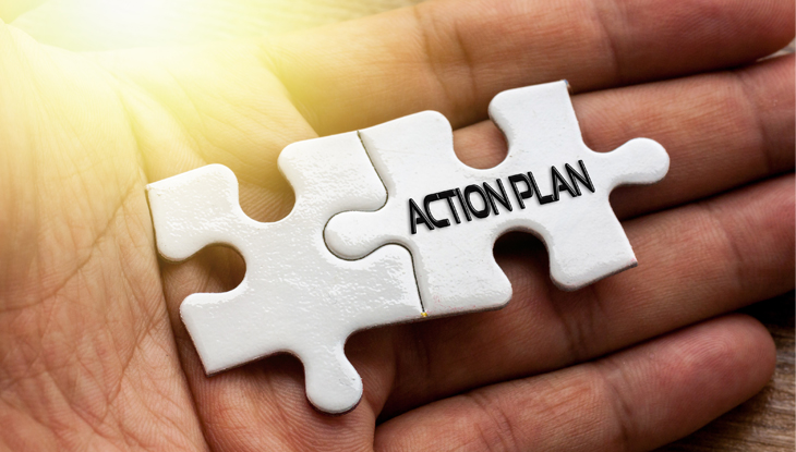 "hand holding two white interlocking puzzle pieces with words ""action plan"" on them"