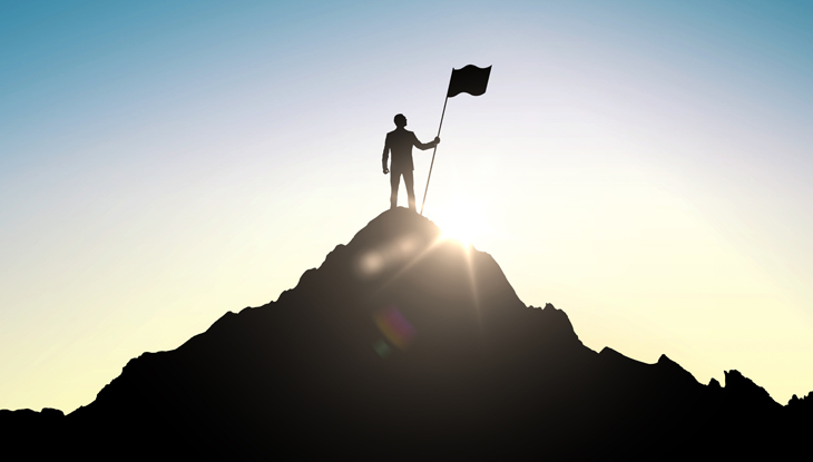 businessman with a flag on a mountain top