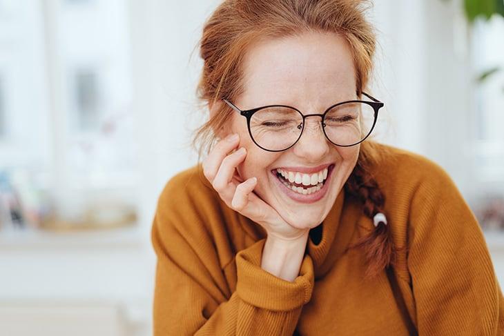 Woman in glasses laughing wearing orange sweater