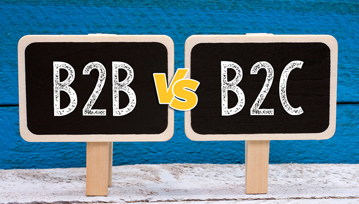 Two chalkboard signs that read B2B vs B2C stand in front of blue wood background.