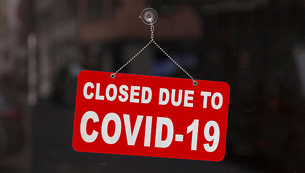 """Sign on front door of business that reads """"Closed Due To Covid-19"""""""