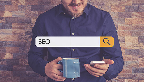 Male with beard looking at phone while holding coffee cup with SEO search bar on top of image