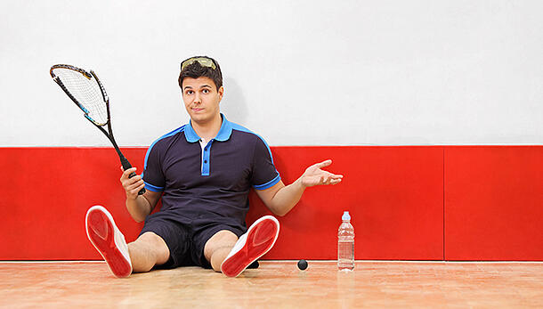 Racquetball player sitting on ground with broken racquet